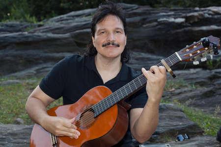 nylon string: Hispanic man playing guitar outdoors in park. Stock Photo