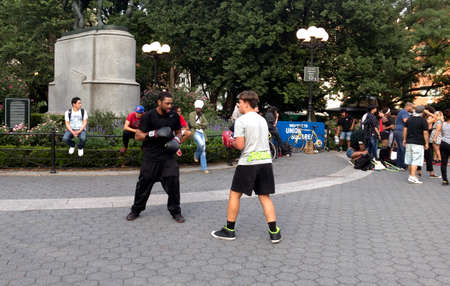 NEW YORK, NEW YORK, USA - AUGUST 25: Two men practice boxing in Union Square park and 14th street.  Taken August 25, 2017 in New York.
