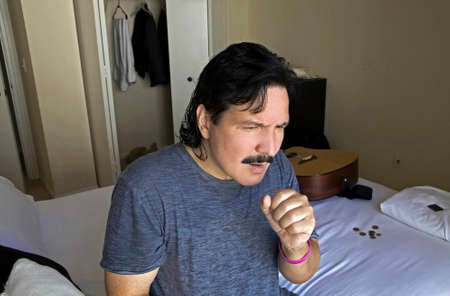 Hispanic man sitting on bed in his bedroom and holding his hand over his mouth to cough.