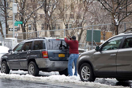 BRONX, NEW YORKUSA - March 2, 2018: Man cleans his car of snow after storm.