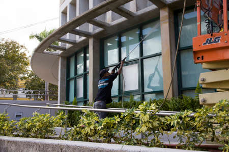 BAYAMON/PUERTO RICO - February 26, 2019: Hispanic man uses high pressure washer machine to clean exterior of building glass.