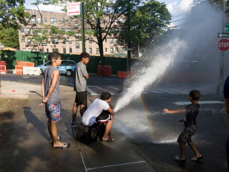 BRONX, NEW YORK/USA - July 20, 2019: Kids play with water from open fire pump in hot summer.