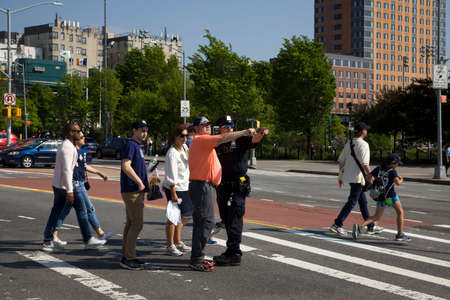 BRONX, NEW YORK/USA - May 19, 2019: Police officer assists man with directions after Yankee baseball game.