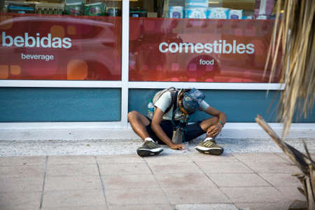 BAYAMON, PUERTO RICOUSA - February 10, 2019: Young man sits outdoors and begs for money. 報道画像