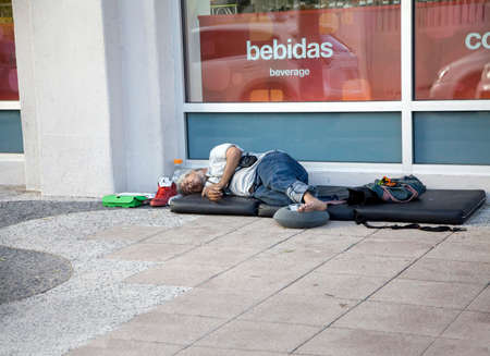 BAYAMON, PUERTO RICOUSA - February 10, 2019: Pan handling man sleeps on a mat on the sidewalk.