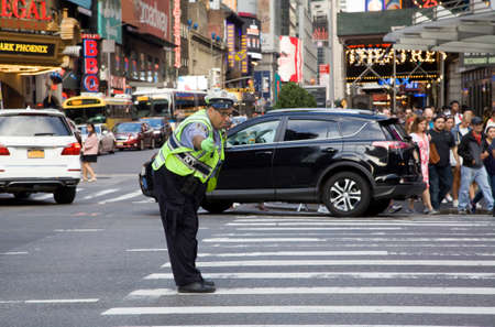 NEW YORK, NEW YORK/USA - July 2, 2019: NYPD traffic agent does his work while adding a touch of style and humor to brighten up busy NYC street.