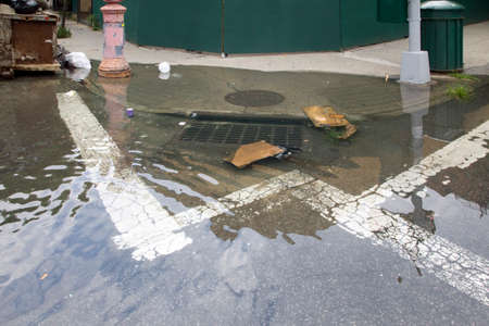 Sewage drain is clogged causing flooding on community corner street in the Bronx, New York.