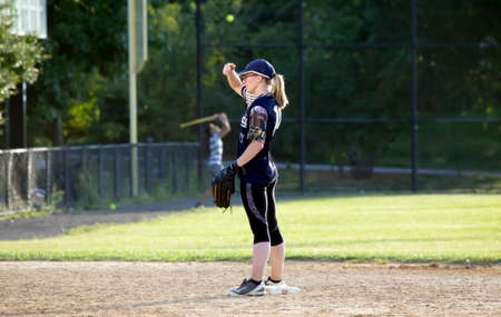 BRONX, NEW YORKUSA - August 10, 2019: Female pitcher uses hand to cover glare during game in public park near Yankee Stadium. Publikacyjne