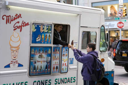 NEW YORK, NEW YORKUSA - May 7, 2018: Young boy buys ice cream cone from truck vendor. Редакционное