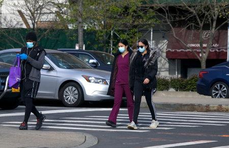 BRONX, NEW YORK/USA - April 20, 2020: Women cross street while wearing surgical masks during Coronavirus pandemic.