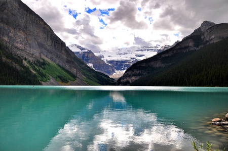 Rocky mountains reflected on Lake Louise blue water