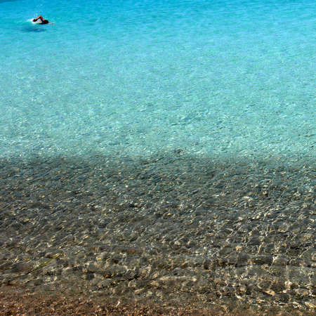 man swimming in crystal sea of Sardinia Stock Photo