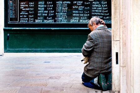 VENICE, ITALY - APRIL 01, 2012: worried beggar on his knees asks for charity in the historical city of Venezia in Italy, famous UNESCO World Heritage Site, in a spring day on April 01, 2012 in Venice