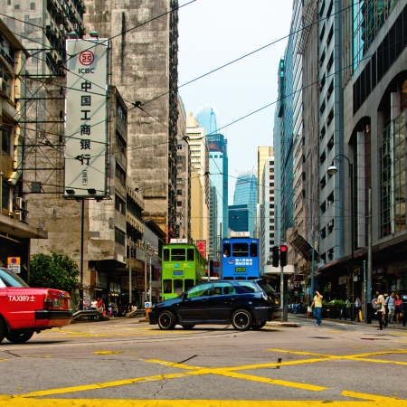 Hong Kong S.A.R., China - July 30, 2012: Street view with typical taxi, shops and tall buildings on July 30, 2012 in Hong Kong, China. With 7M population and land mass of 1104 sq km, it is one of the most dense areas in the world.