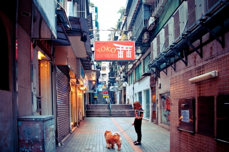 MACAU - AUGUST 1, 2012: person with dog walking in narrow street on August 1, 2012 in Macau, China. The Historic Centre of Macao was inscribed on the UNESCO World Heritage List in 2005