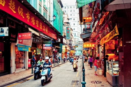 Macau, China - August 1, 2012: tourists and shoppers walking along a narrow street in central Macau with many shops and restaurants