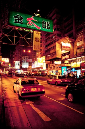 Hong Kong S.A.R., China - August 02, 2012: signs, people and taxis at night on Nathan Road in Kowloon, Hong Kong Editorial