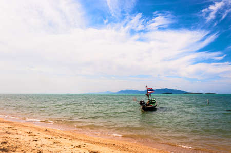 typical fisherman boat with national flag, beach and sea in Koh Samui, Thailand photo