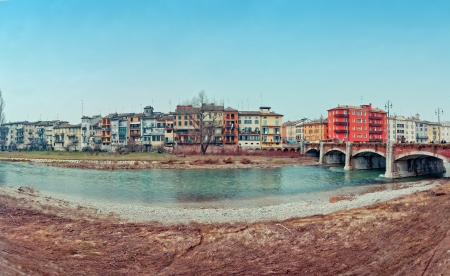 Parma river with typical city houses and bridge in winter day