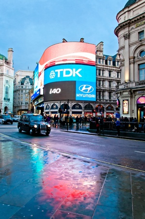 tdk: LONDON - APRIL 12  Famous Piccadilly Circus neon signage reflected on street with taxy on April 12, 2013 in London, United Kingdom  Piccadilly Circus neon signage has become a major attraction of London