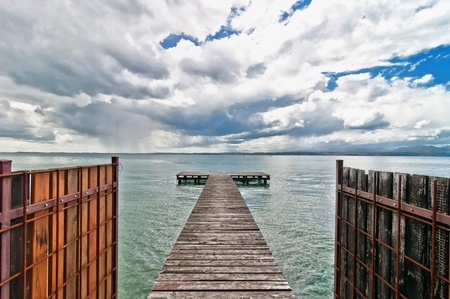 wooden pier and cloudy dramatic sky over Garda lake - Italy photo