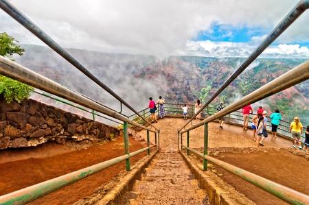 KAUAI, HAWAII -  AUGUST 30, 2013 - tourists admire Waimea canyon from Waimea Lookout observation deck in Kauai, the oldest of the main Hawaiian islands