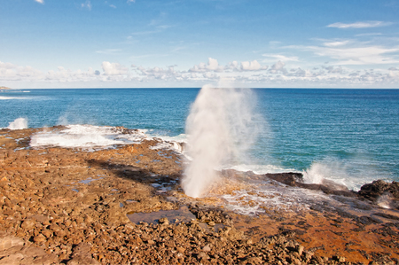 gush: Rush of ocean water being spewed out of Spouting Horn, a natural blow hole created by a volcanic lava tube on the island of Kauai south shore in Hawaii