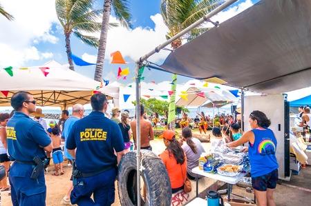locals: Honolulu, HI, USA - September 7, 2013  policemen, tourists and locals in Waikiki beach market in Honolulu, Hawaii  Waikiki white sand beach shoreline is Hawaii s most famous beach
