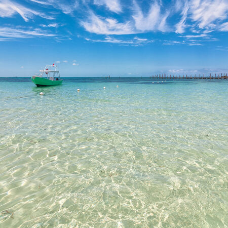 mujeres: tropical sea and boat on famous Playa del Norte beach in Isla Mujeres, Mexico