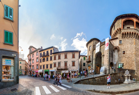 quoted: CASTELNUOVO GARFAGNANA, ITALY - AUGUST 09, 2014: tourists visit the main square in Castelnovo Garfagnana, Italy. The village is quoted for the first time in a 8th century official document