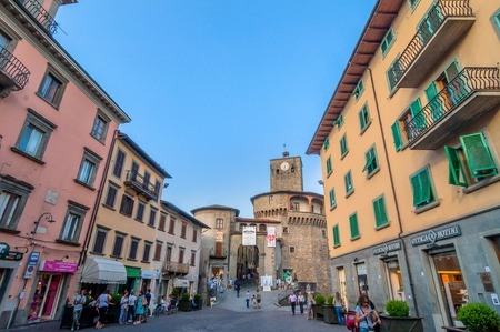 CASTELNUOVO GARFAGNANA, ITALY - AUGUST 09, 2014: tourists visit the main square in Castelnovo Garfagnana, Italy. The village is quoted for the first time in a 8th century official document