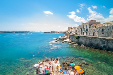 ortigia: SYRACUSE, ITALY - AUGUST 17, 2014: tourists and locals enjoy blue mediterranean sea in Ortigia, Syracuse, Italy. Ortigia is a small island which is the historical centre of the city of Syracuse, Sicily. Editorial