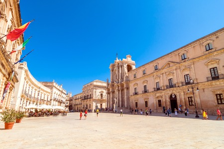ortigia: SYRACUSE, ITALY - AUGUST 16, 2014: tourists and locals visit main square Piazza del Duomo in Ortigia, Syracuse, Italy. Ortigia is a small island Which is the historical center of the city of Syracuse, Sicily.