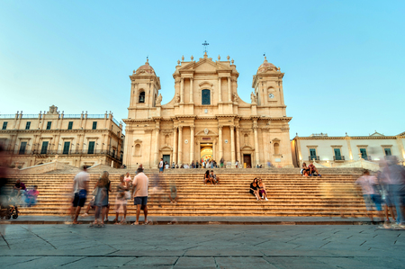 known: NOTO, ITALY - AUGUST 18, 2014: tourists in front of Baroque Cathedral in Noto, Sicily. Built in 1776, Considered the jewel of European Baroque, partially collapsed During 1996 earthquake. In 2002 Noto and its church were declared a UNESCO World Heritage S