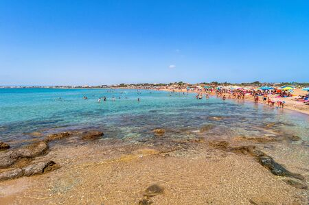 capo: PORTOPALO, ITALY -  AUGUST 19, 2014: tourists and locals enjoy blue sea on Isola delle Correnti beach in Portopalo, Sicily, Italy. Isola delle Correnti is a place in the southern-eastern corner of Sicily where the two sea, Mediterranean and Ionian, meet.