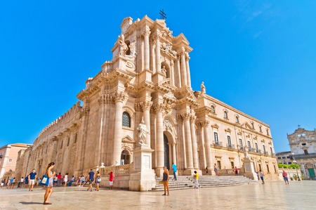 SYRACUSE, ITALY - AUGUST 16, 2014: tourists and locals visit main square Piazza del Duomo in Ortigia, Syracuse, Italy. Ortigia is a small island which is the historical centre of the city of Syracuse, Sicily. Editorial