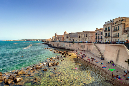 syracuse: SYRACUSE, ITALY - AUGUST 17, 2014: tourists and locals enjoy blue mediterranean sea in Ortigia, Syracuse, Italy. Ortigia is a small island which is the historical centre of the city of Syracuse, Sicily. Editorial