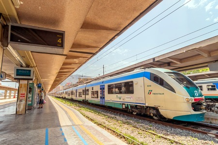 palermo   italy: PALERMO, ITALY - AUGUST 21, 2014: passenger on platform and local train at railway station in Palermo, Italy.  The station is owned by the Ferrovie dello Stato, the national rail company of Italy. Editorial
