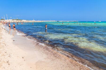 capo: SAN VITO LO CAPO, ITALY - AUGUST 22, 2014: tourists and locals enjoy blue mediterranean sea in San Vito Lo Capo, Italy. This small town is located in a valley between spectacular mountains, and its famous beach has been elected best italian beach on TripA Editorial