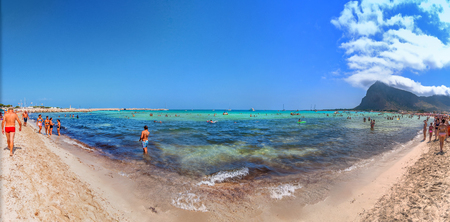 elected: SAN VITO LO CAPO, ITALY - AUGUST 22, 2014: tourists and locals enjoy blue mediterranean sea in San Vito Lo Capo, Italy. This small town is located in a valley between spectacular mountains, and its famous beach has been elected best italian beach on TripA Editorial