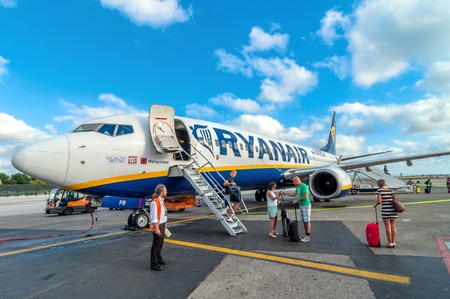PISA, ITALY - AUGUST 21, 2014: passengers deplane Ryanair Jet airplane after landing in Pisa airport, Italy. Ryanair is the biggest low-cost airline company in the world.