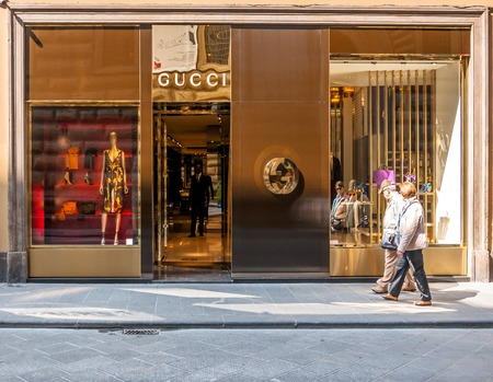 gucci shop: FLORENCE, ITALY - March 21, 2014: tourists walk in front of Gucci Shop in Florence, Italy. Florence is home to some of the most famous works of art on earth.