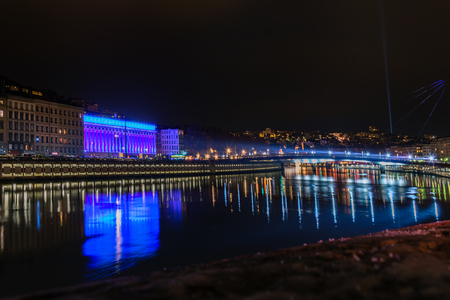origins: LYON FRANCE  DECEMBER 6 2014: street view with city skyline reflected in river during Festival of Lights in Lyon France. The origins of the Fete des Lumieres date to 1643. Editorial