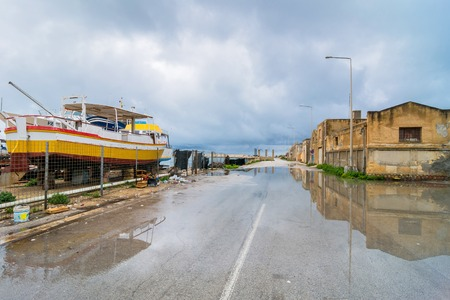 MARSALA, ITALY - FEBRUARY 22, 2014: day view of coastline and street with reflection in Marsala, Italy. The town is famous for the docking of Garibaldi on 11 May 1860 and for its wine.