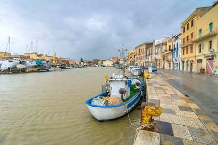 fishing fleet: MAZARA DEL VALLO, ITALY - FEBRUARY 22, 2014: day view of canal, fishing boats and downtown in Mazara del Vallo, Italy. Mazara port gives shelter to the largest fishing fleet in Italy