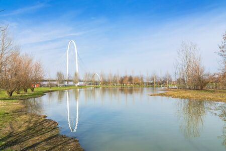 reggio emilia: REGGIO EMILIA, ITALY - MARCH 9, 2015: bridges complex by architect Santiago Calatrava reflected in pound in Reggio Emilia, Italy. The central arch of the bridge is 220 meters long and 50 meters high