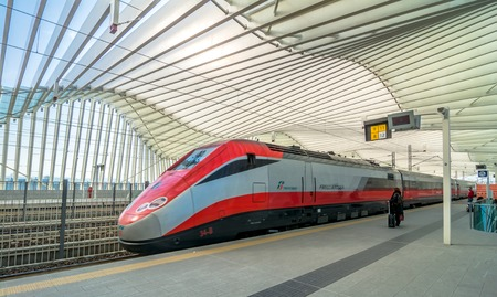 REGGIO EMILIA, ITALY - MARCH 12, 2015: train and passengers in High Speed Train Station in Reggio Emilia, Italy. It is designed by architect Santiago Calatrava and composed of 457 steel frames.