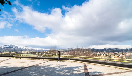 potenza: POTENZA, ITALY - MARCH 13, 2015: unidentified person with dog, panoramic view of city and mountains in Potenza, Italy. Potenza is the highest regional capital city in Italy.