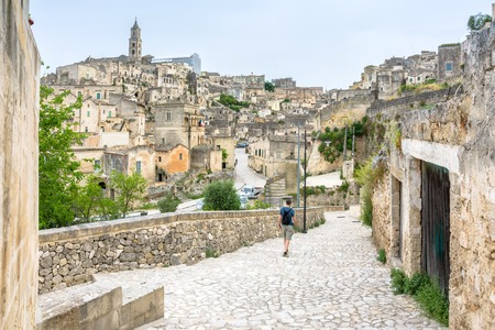 unesco culture heritage: MATERA, ITALY - MAY 15, 2015: tourist walking along stone street in Sassi di Matera ancient town in Matera, Italy. The city is a UNESCO World Heritage site and European Capital of Culture for 2019.