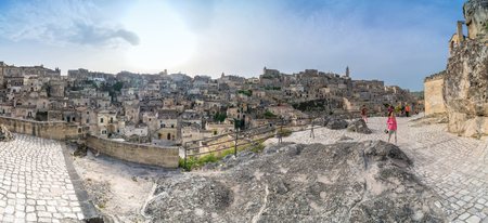 unesco culture heritage: MATERA, ITALY - MAY 15, 2015: panoramic day view of Sassi di Matera ancient town and tourists in Matera, Italy. The city is a UNESCO World Heritage site and European Capital of Culture for 2019.